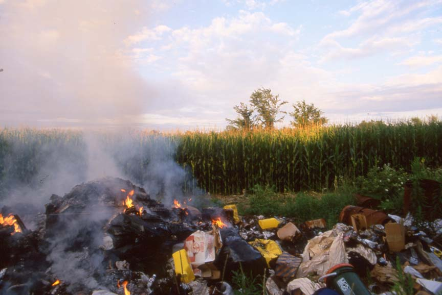 large pile of burning trash beside corn field