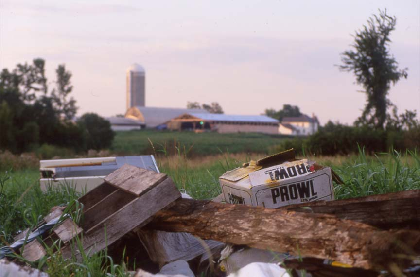 piled trash for burning with dairy farm in background